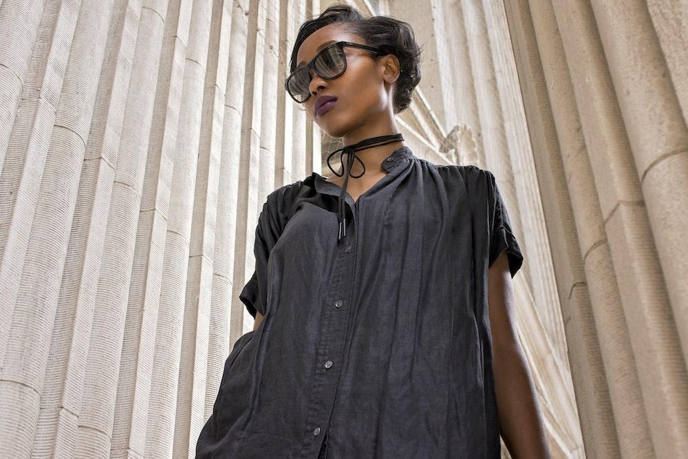 woman wearing black short-sleeved dress near wall
