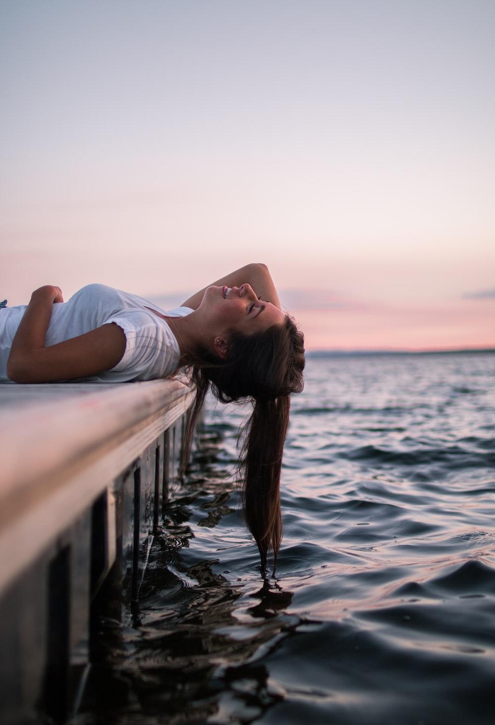 woman lying on white dock