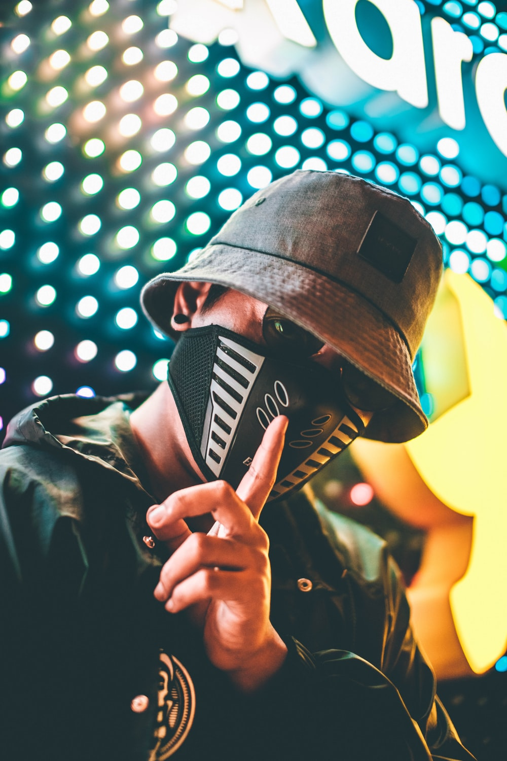 man wearing black bucket hat, mask, and jacket during night time