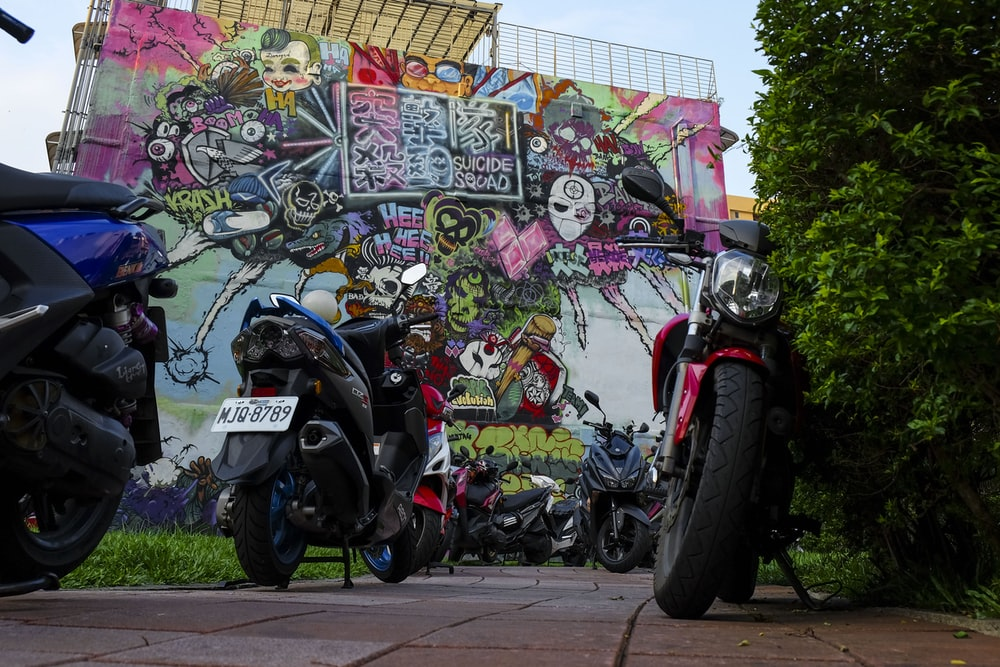 assorted-color motorcycles parking near wall wit graffiti art