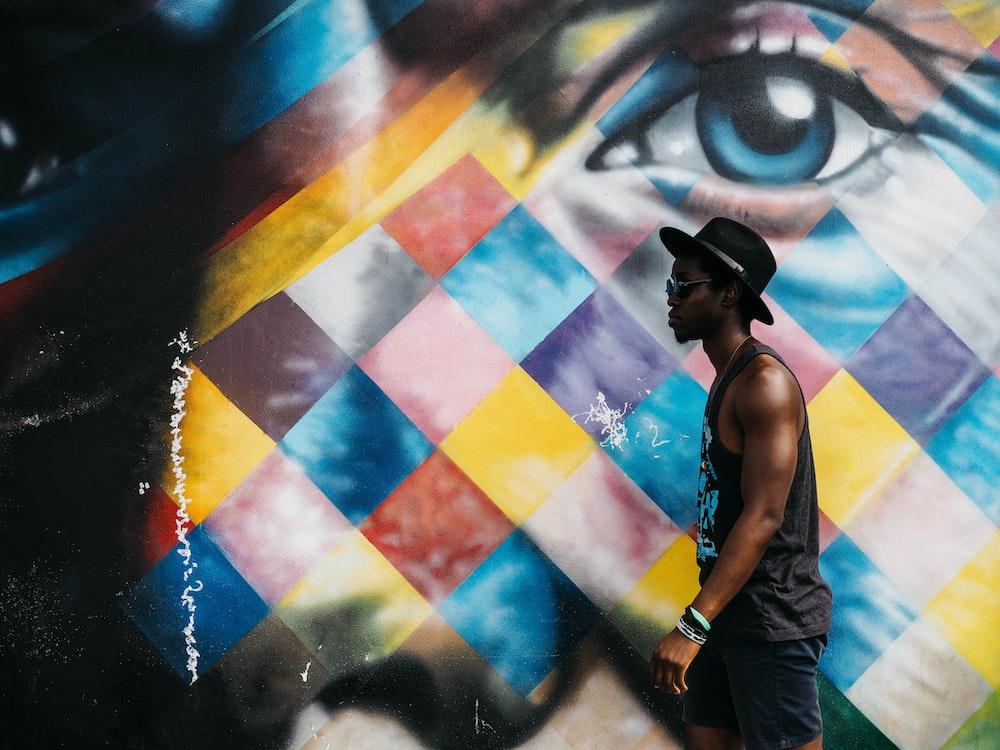 man in black tank top wearing black bucket hat beside wall art
