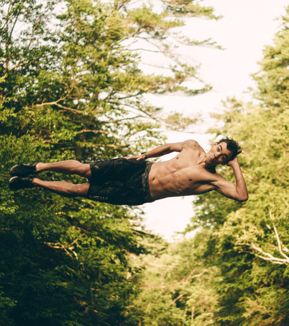 man on mid air near trees at daytime