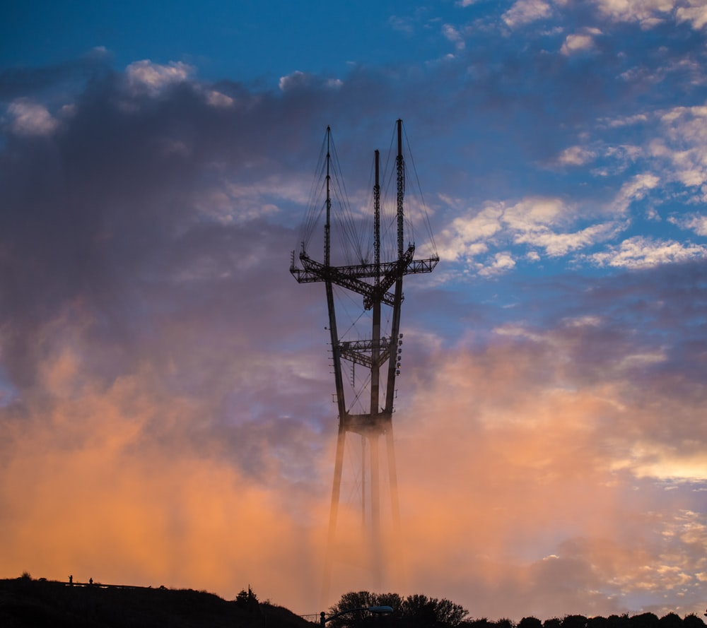 gray transmission tower over the trees