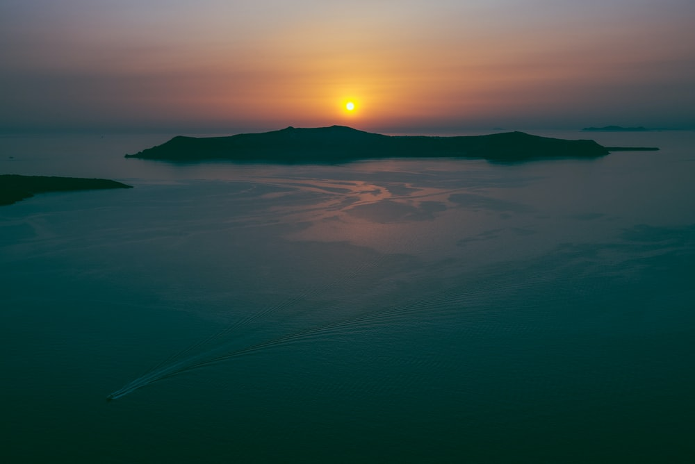 silhouette of island during golden hour aerial photo