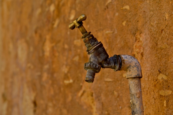 selective focus photography of brown faucet