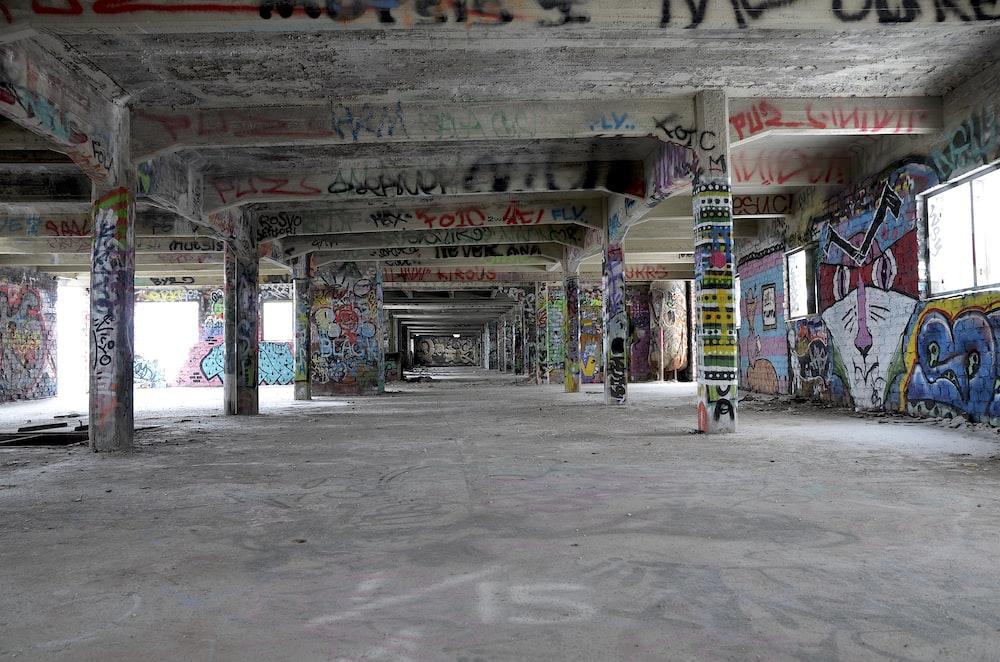 empty hallway full of graffiti on walls