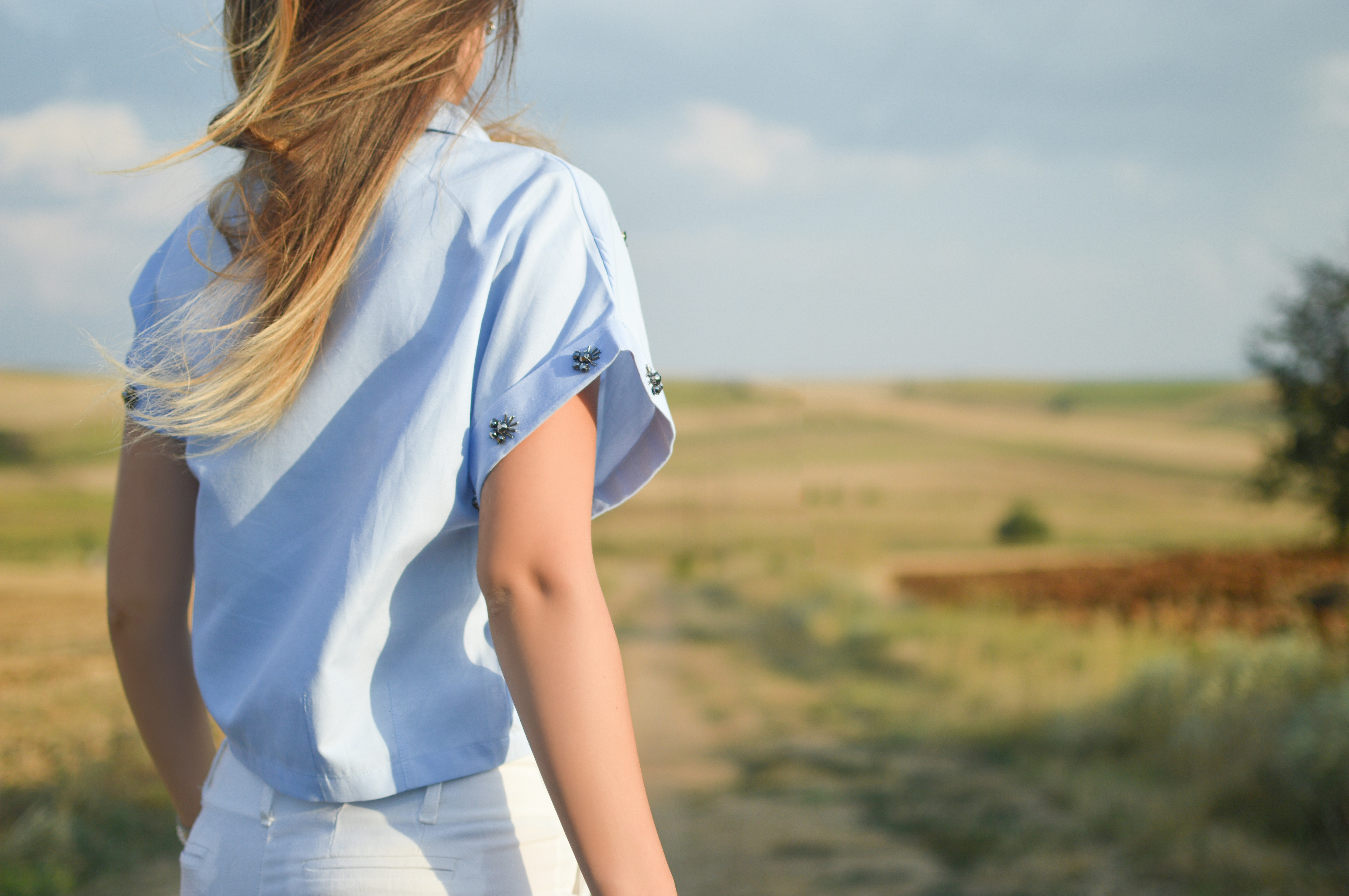 woman wearing white dress shirt standing on green grass field during day time