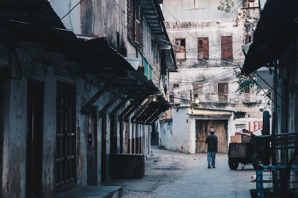 man walking near brown wooden cart between gray concrete buildings during daytime