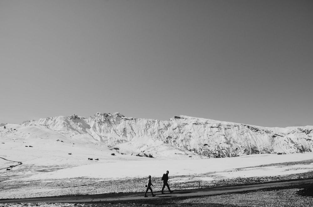 grayscale photography of two people walking near mountain covered snow