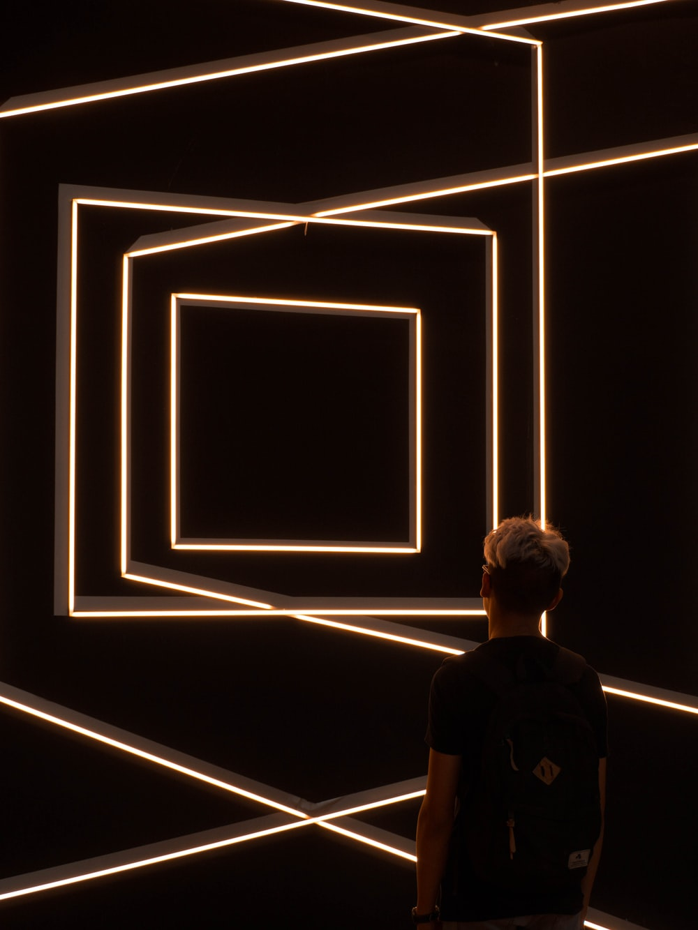 person standing in front of optical illusion wall