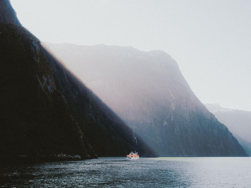 white boat sailing near montain