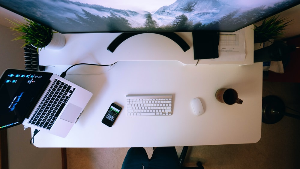 turned on laptop near smartphone and Apple keyboard and Magic Mouse on white computer desk