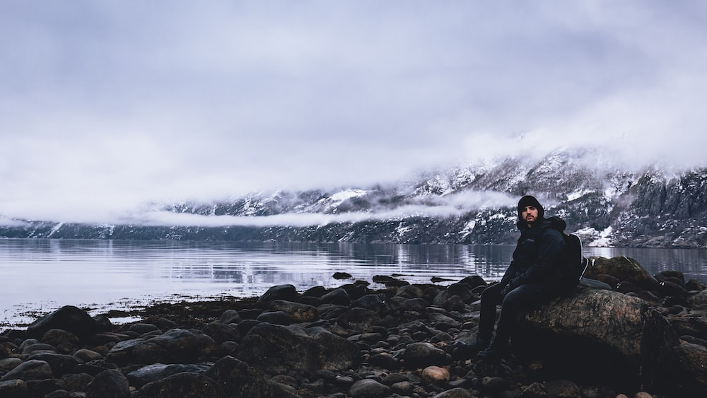 man sitting on rock overlooking calm body of water under white cloudy skies at daytime