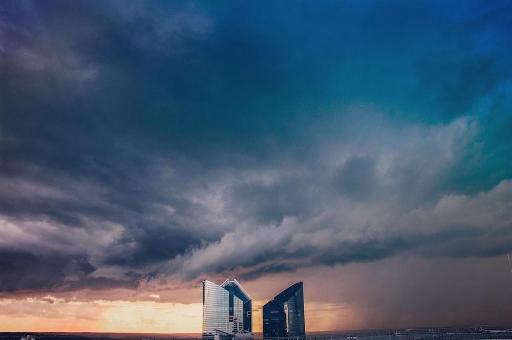 three high-rise buildings under dark sky