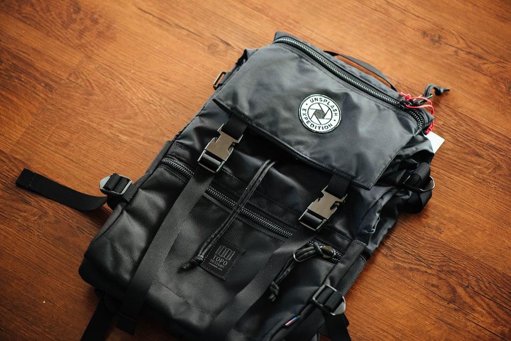 black backpack on wooden deck