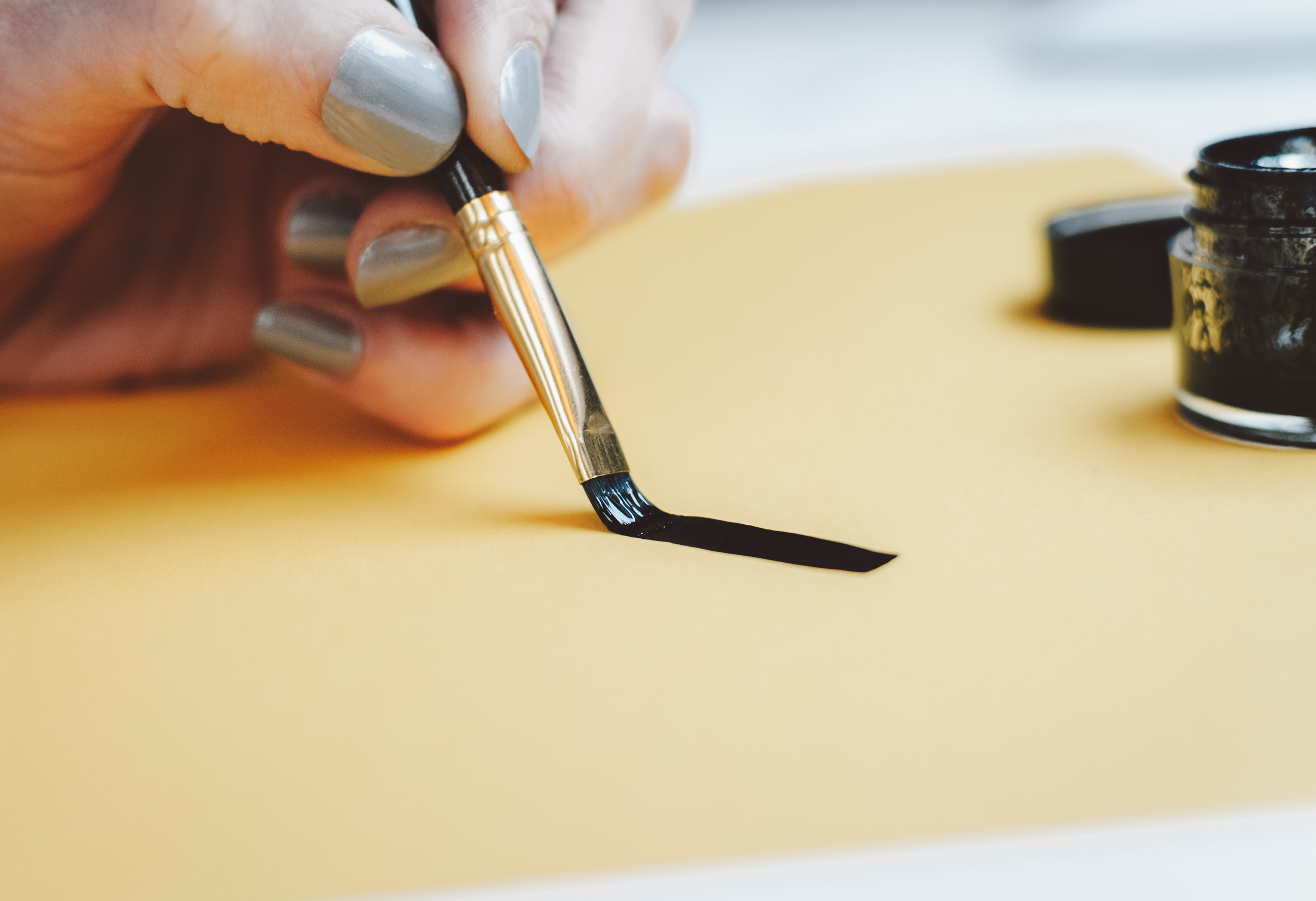 person writing on beige paper using black ink
