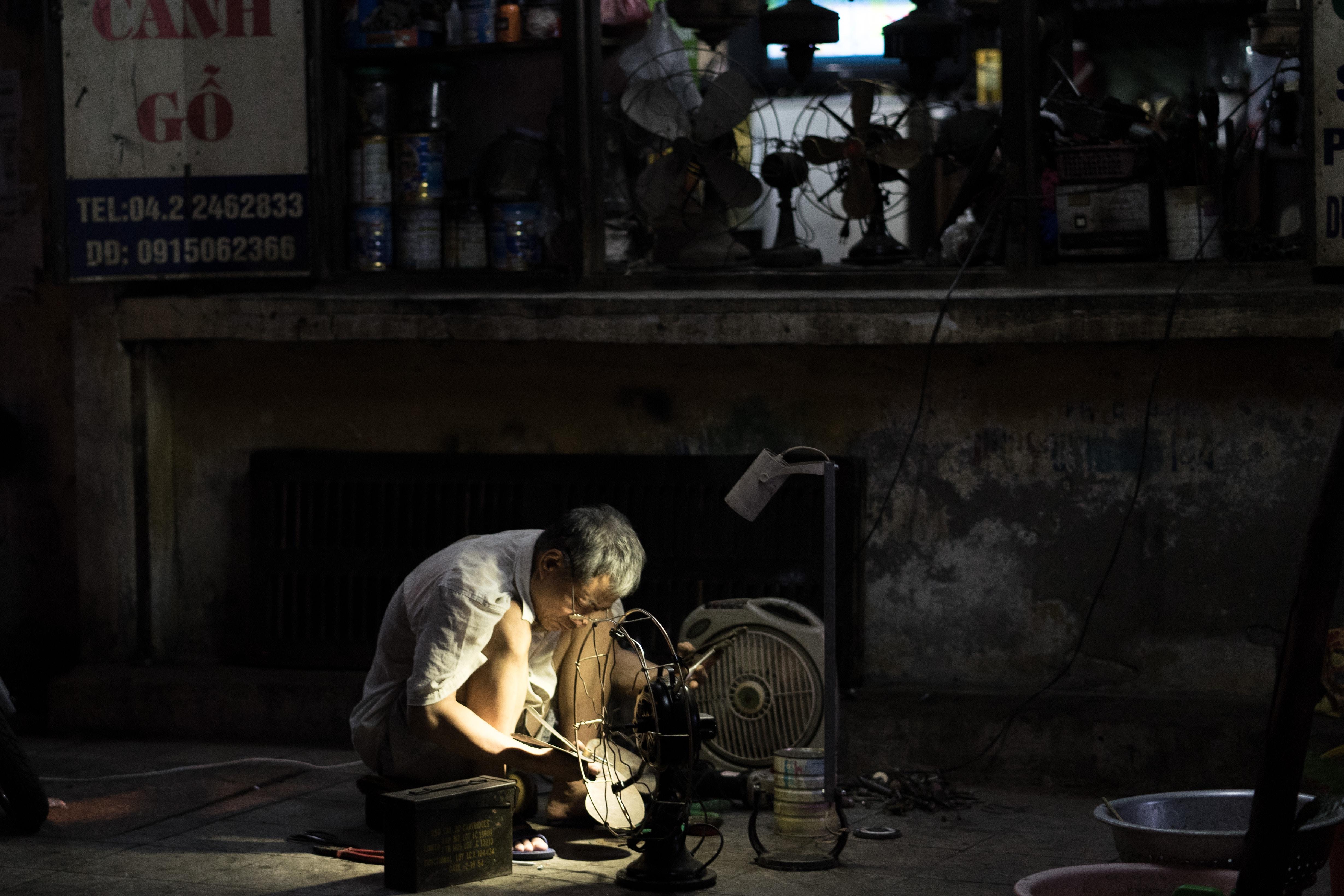 man in gray dress shirt beside black desk fan