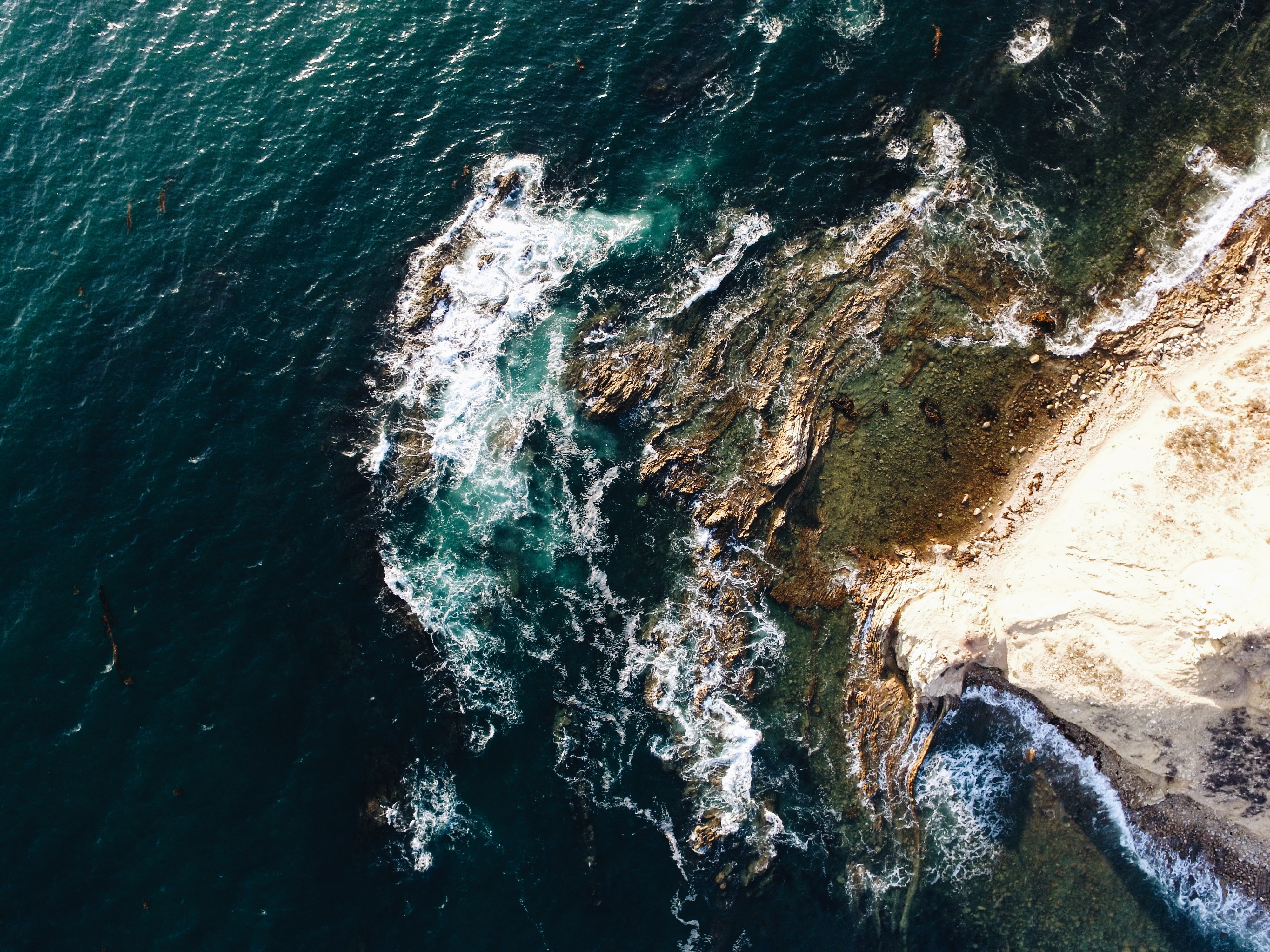 aerial photography of brown rocky shoreline at daytime