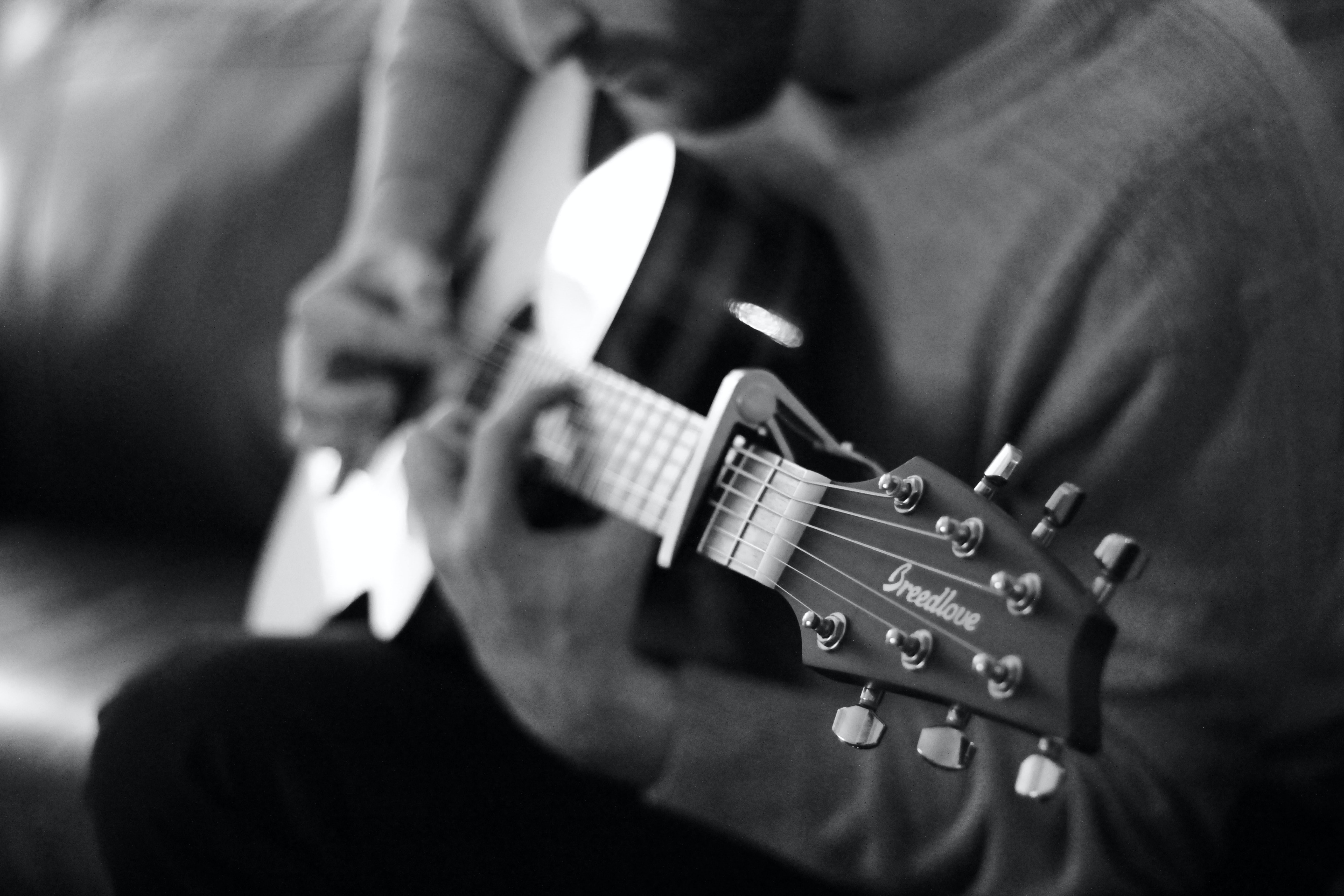 man playing guitar grayscale photo