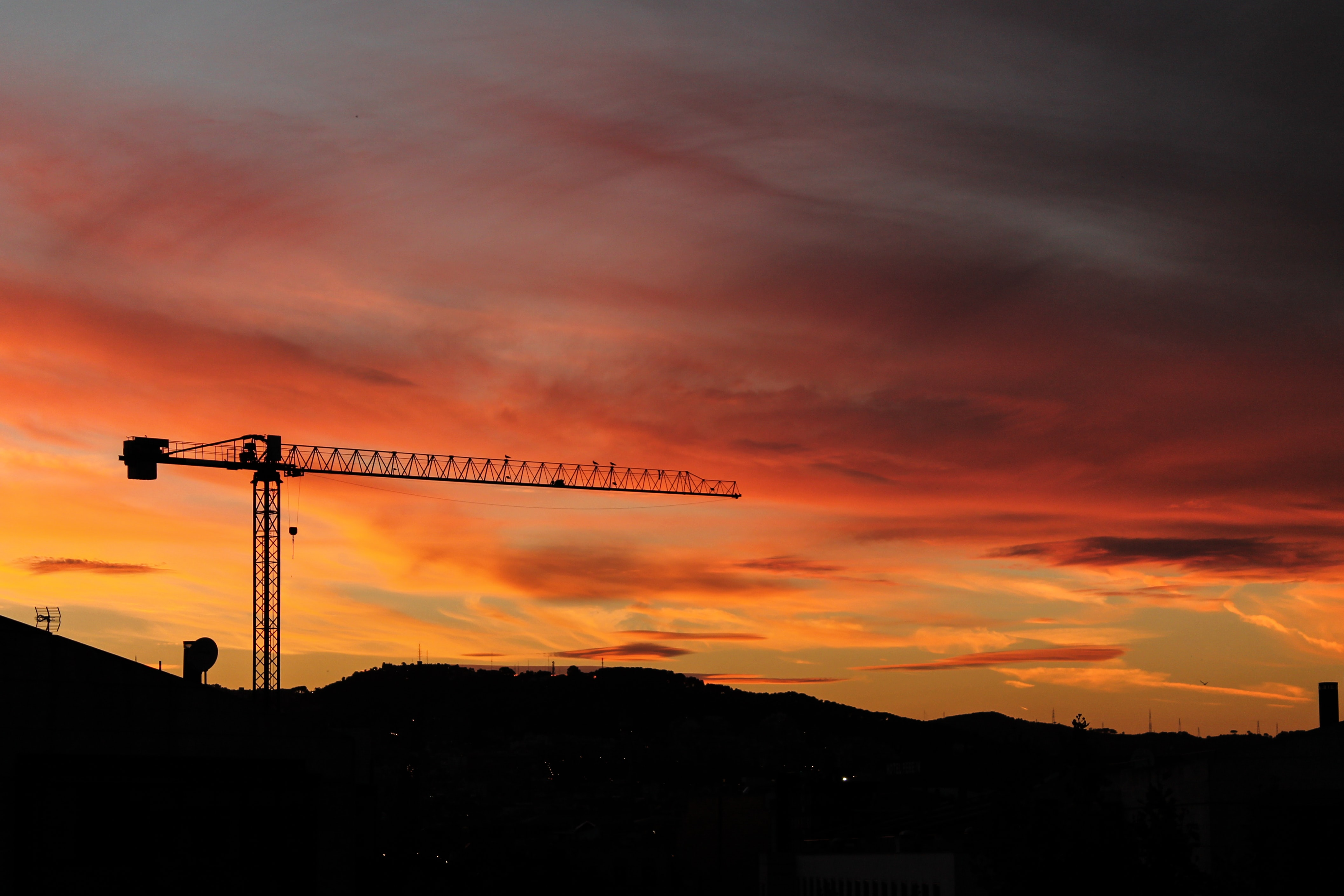 silhouette of crane and hill under cloudy sky photo taken during sunset
