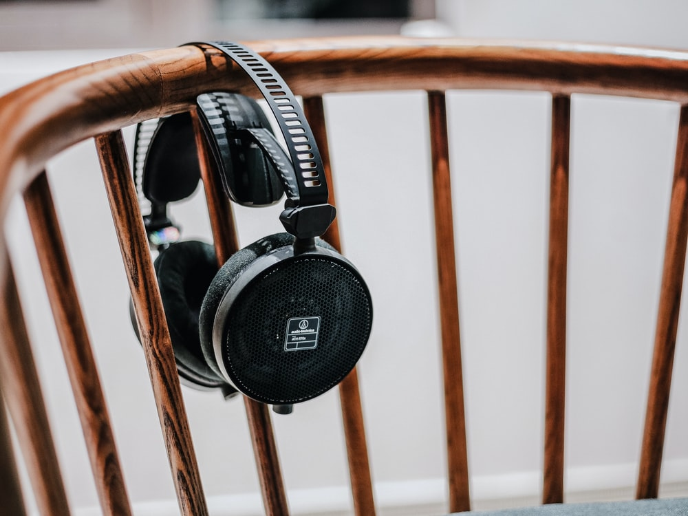 black cordless headphones on brown wooden chair
