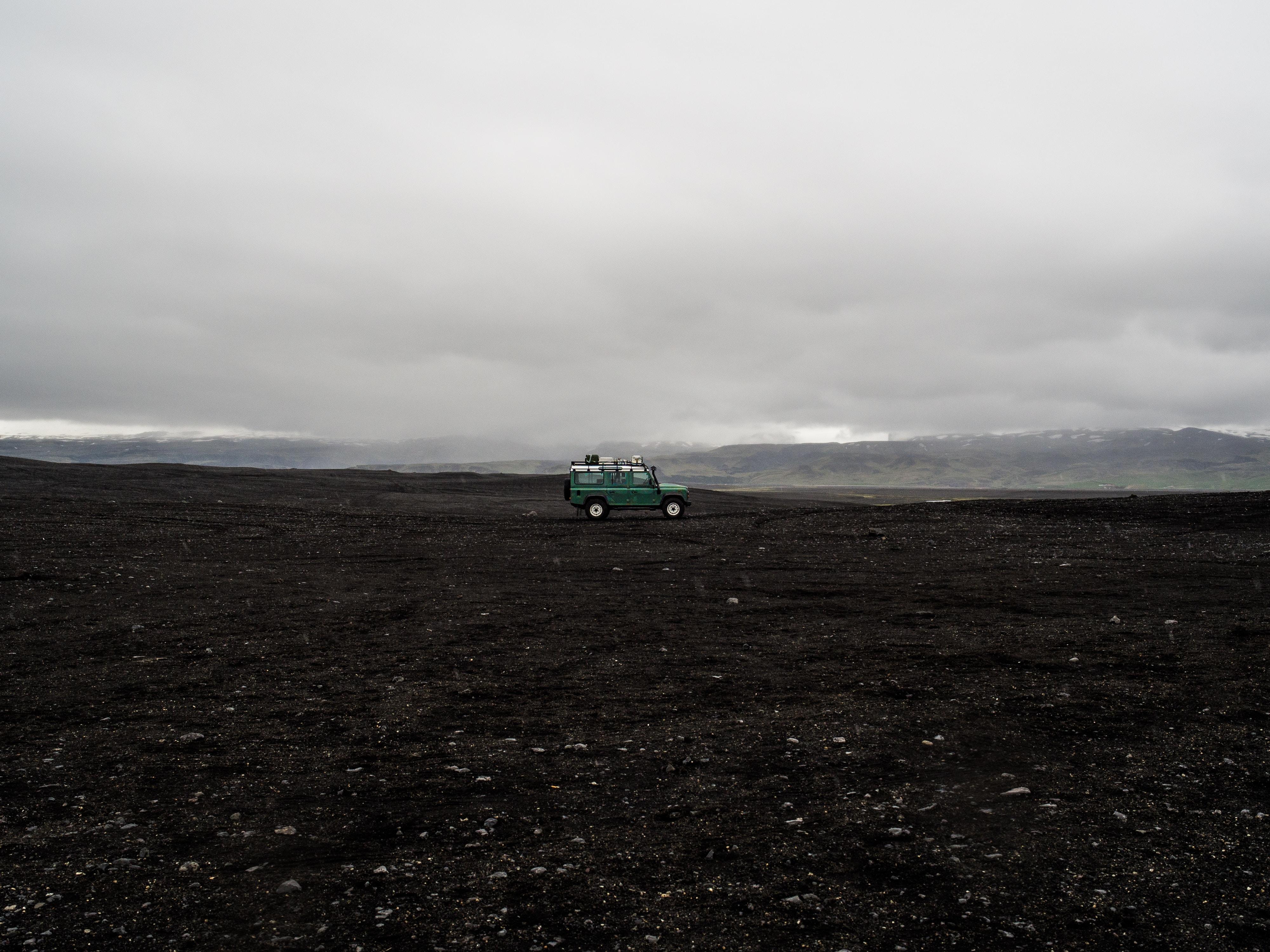 green SUV on black soil taken at daytime