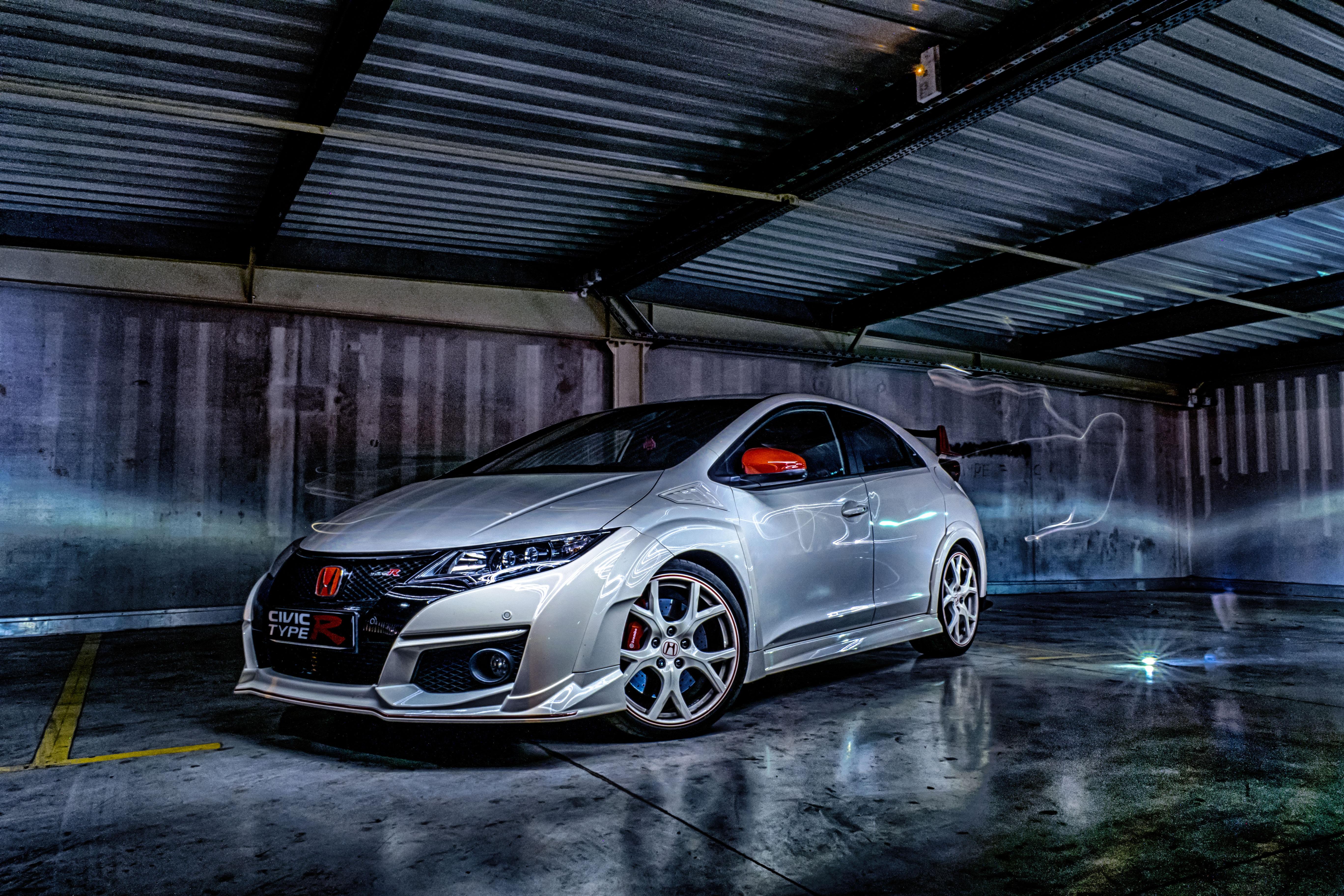 silver Honda 3-door hatchback inside gray garage
