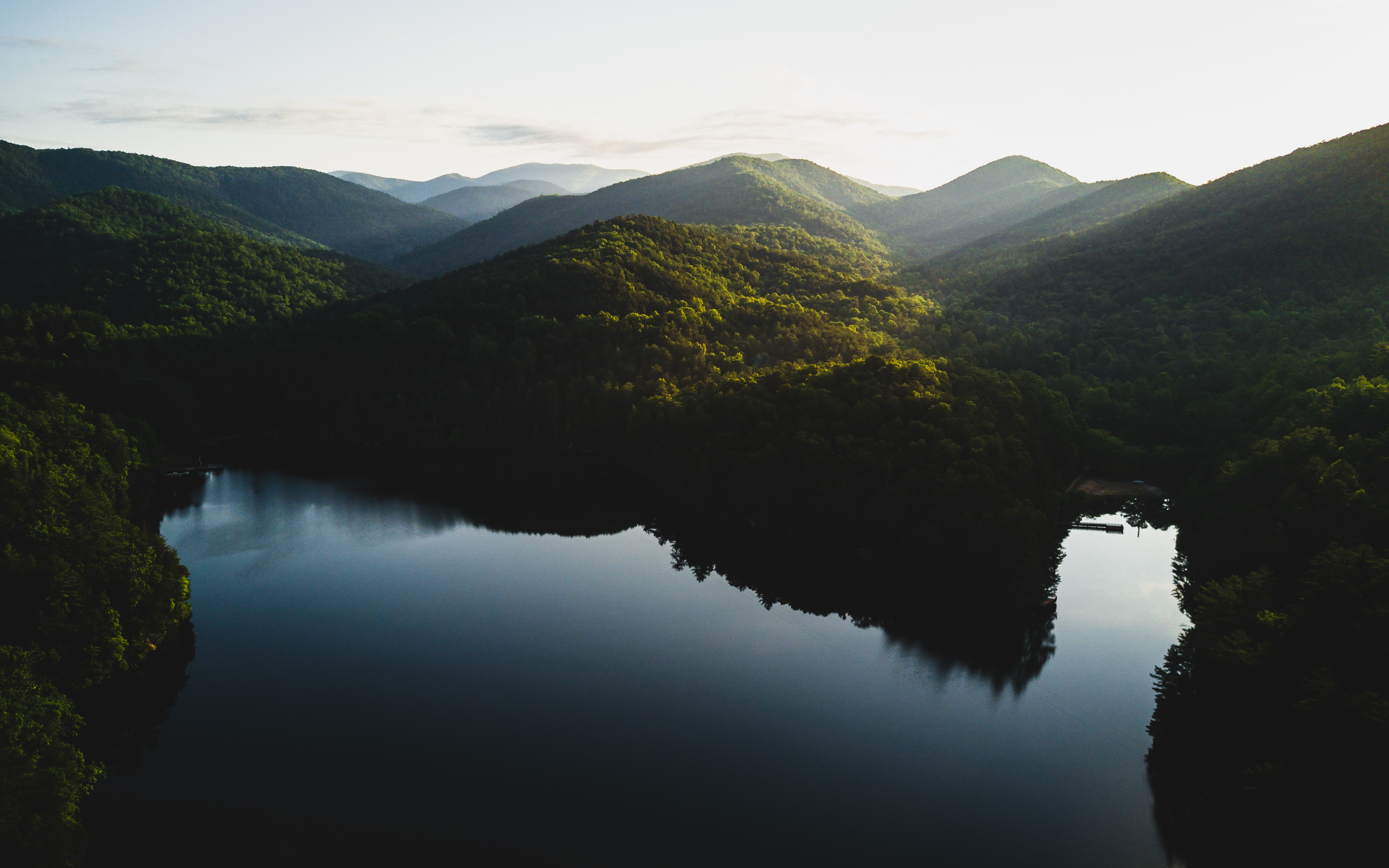 mountains surrounded by body of water during daytime