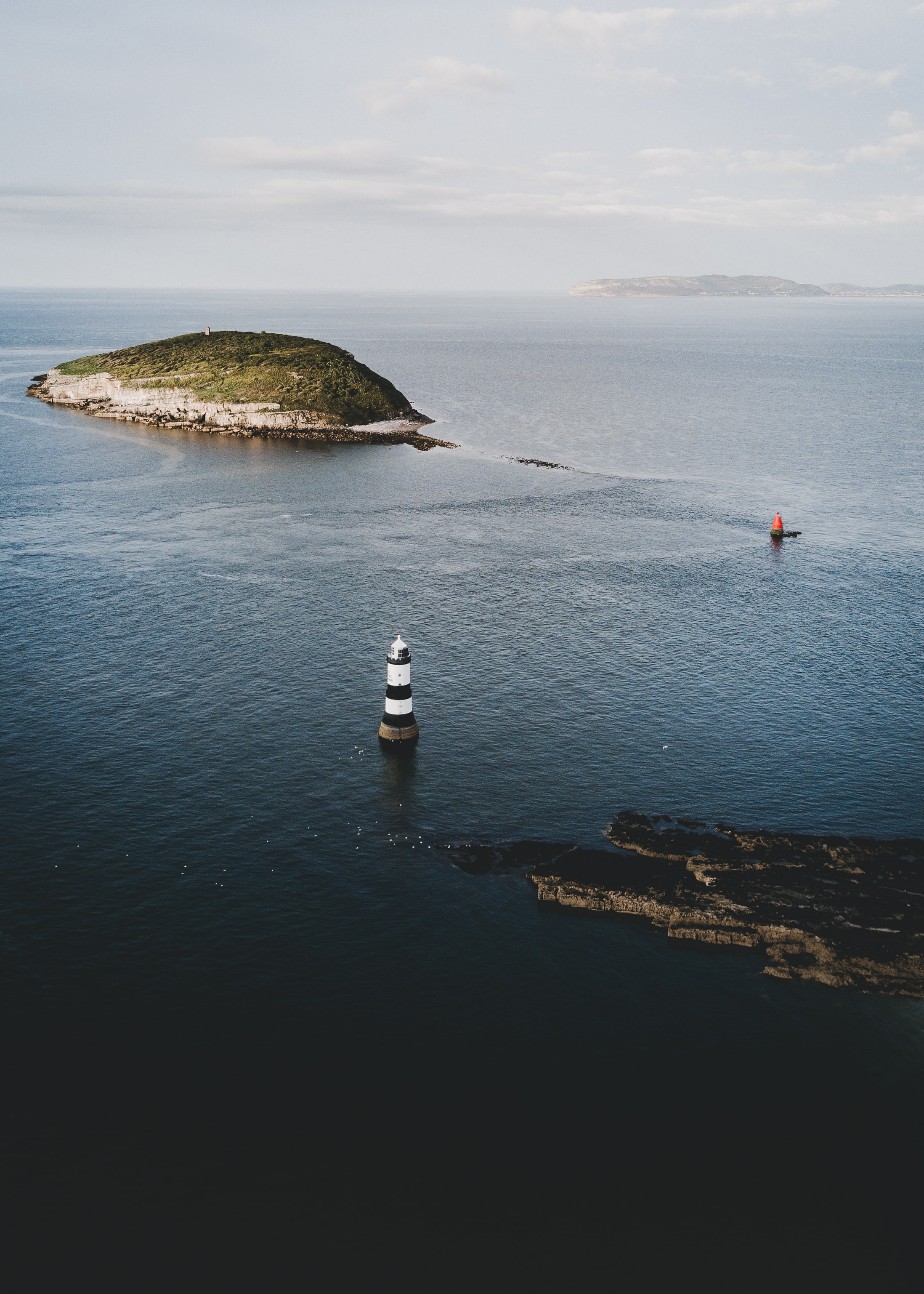 lighthouse surrounded by body of water near island