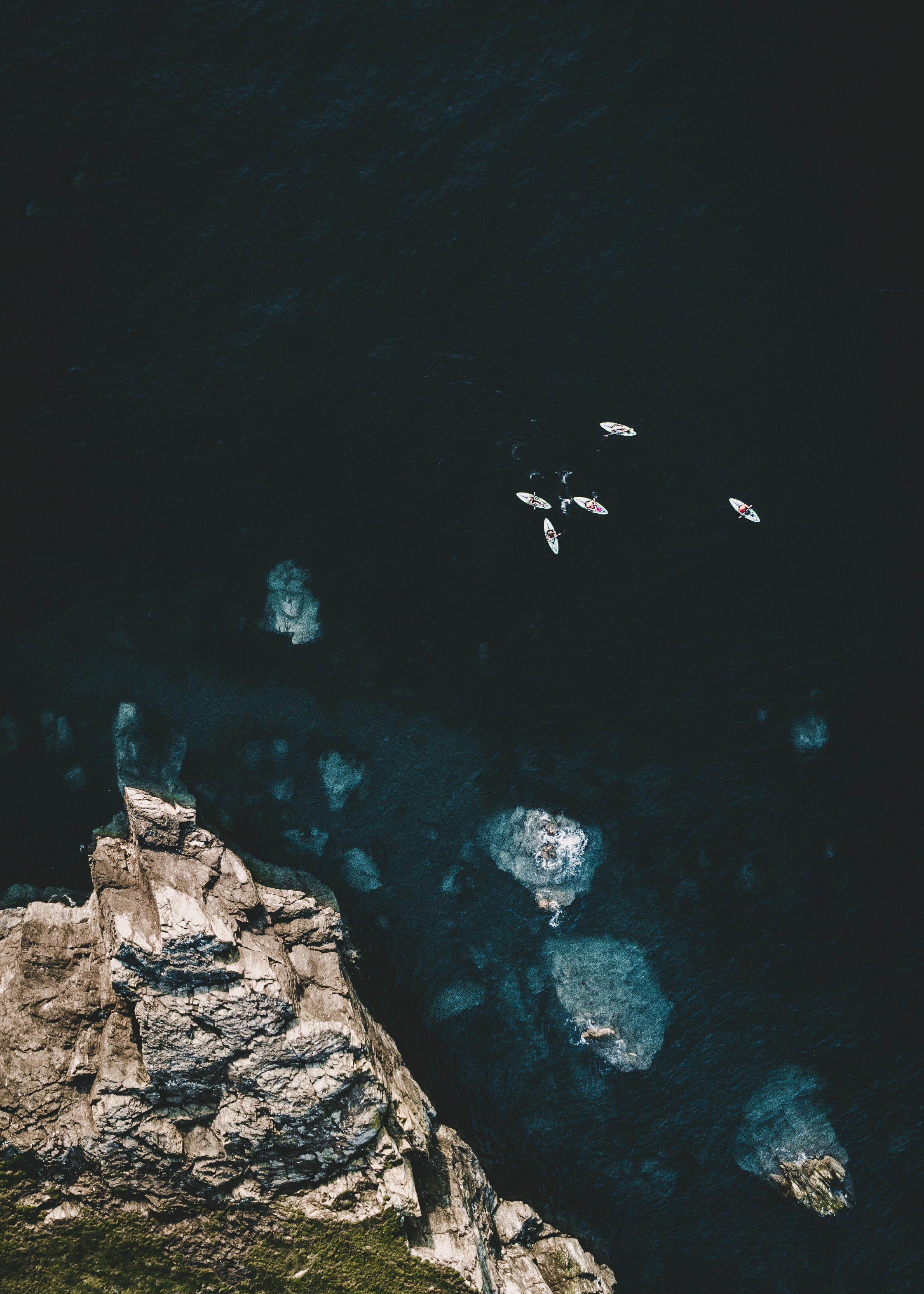 aerial photo of kayaks on water near brown cliff