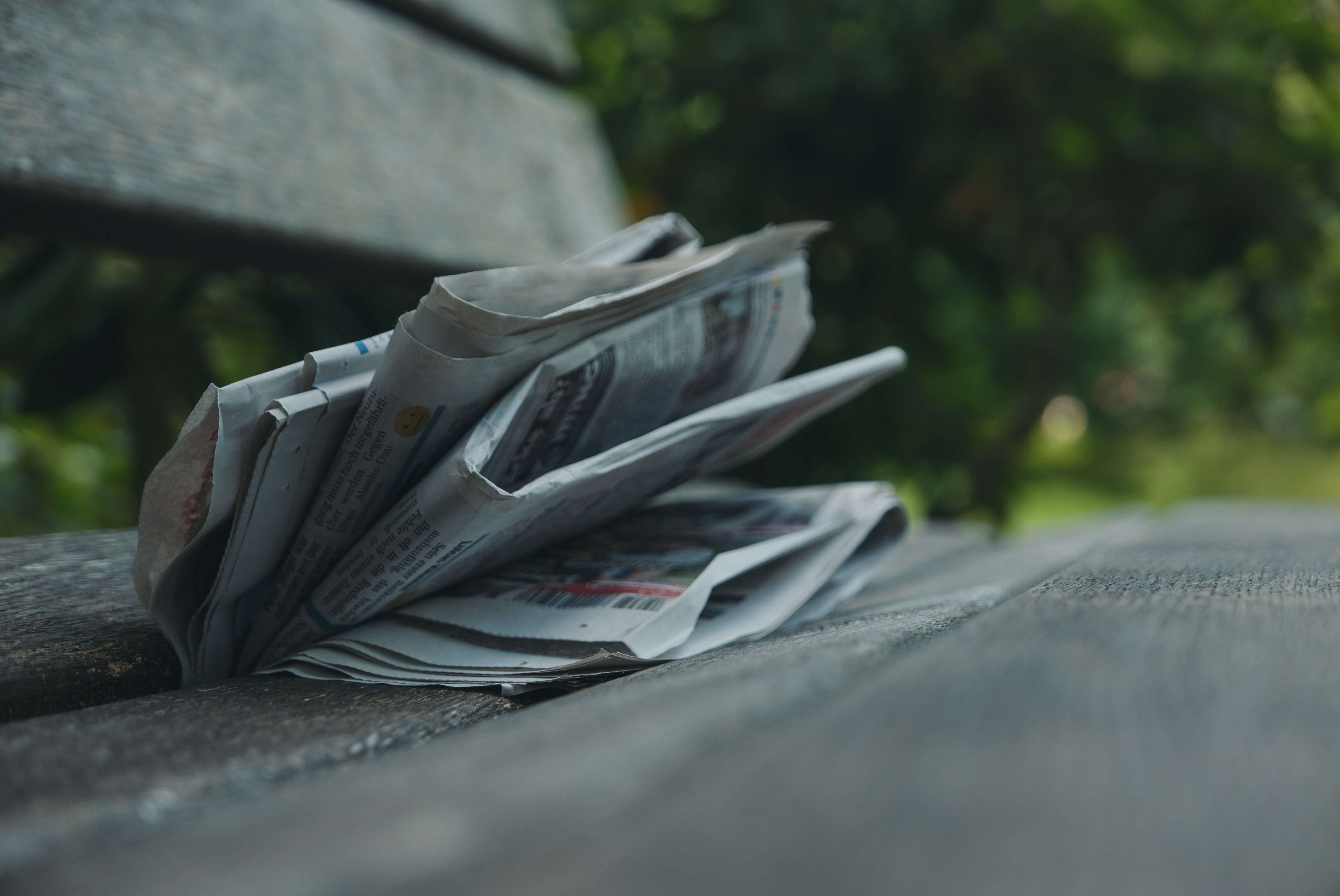 selective focus photography of newspaper on gray surface