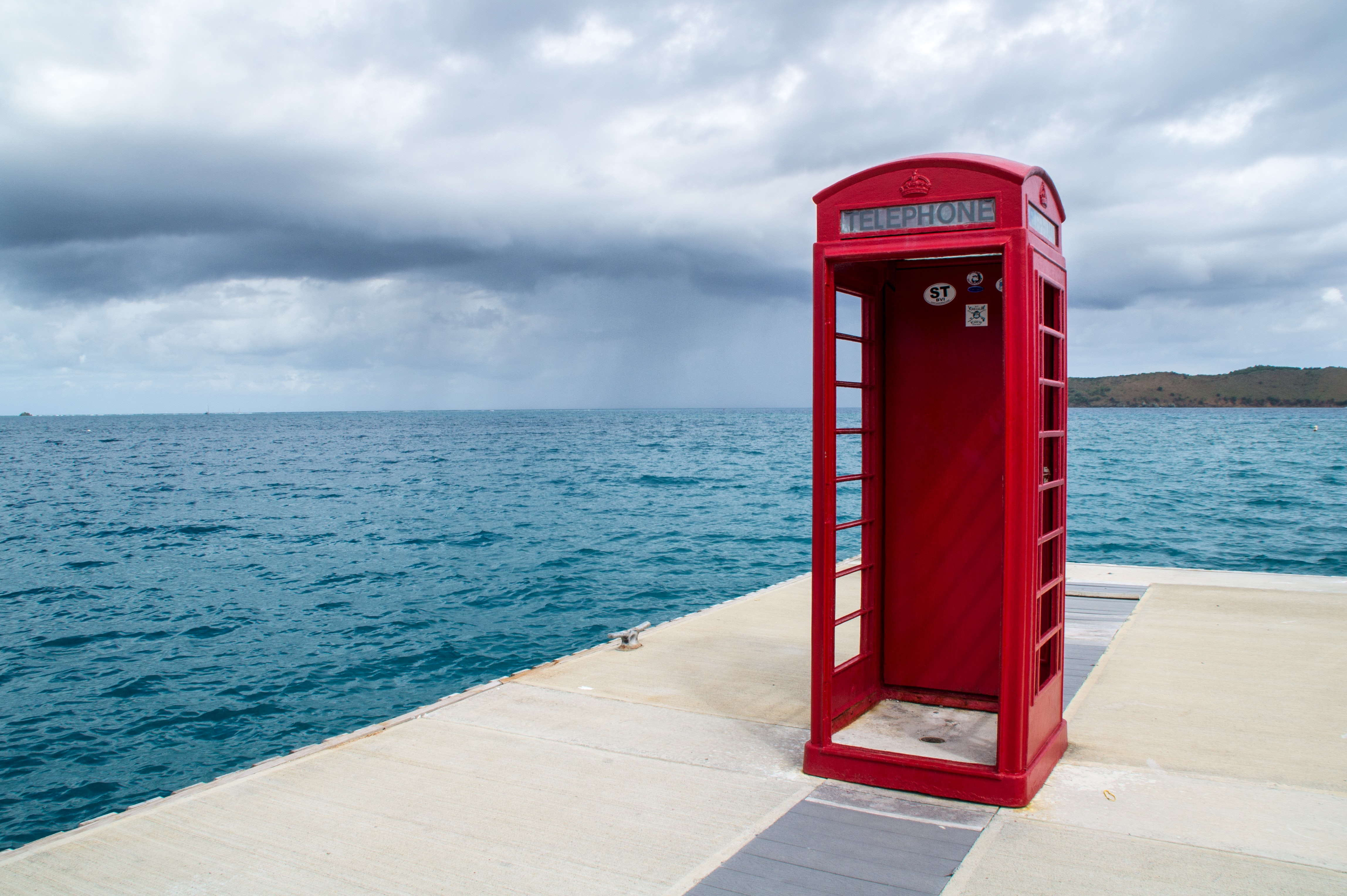 red telephone booth near body of water