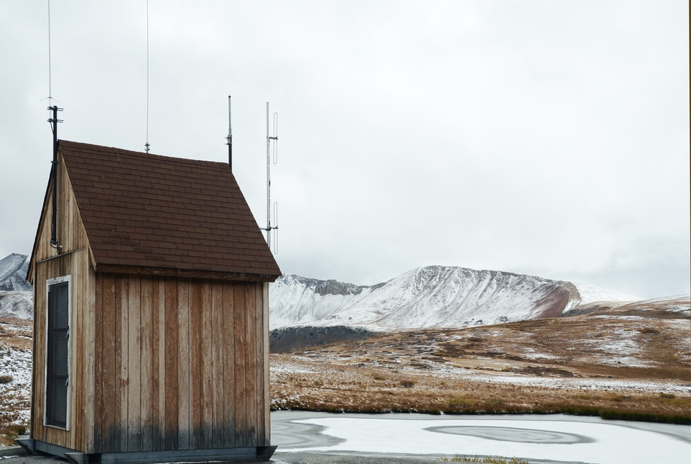brown wooden shed near snow-covered land during daytime