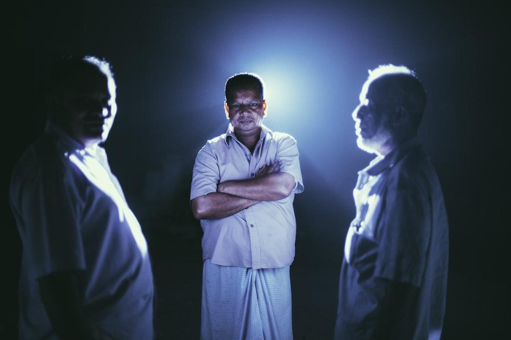 man standing between two men