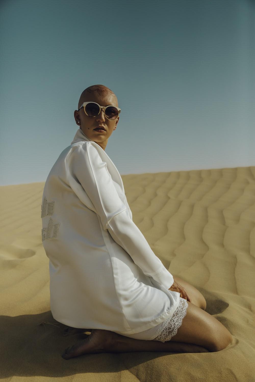 woman kneeling on brown sand taken at daytime
