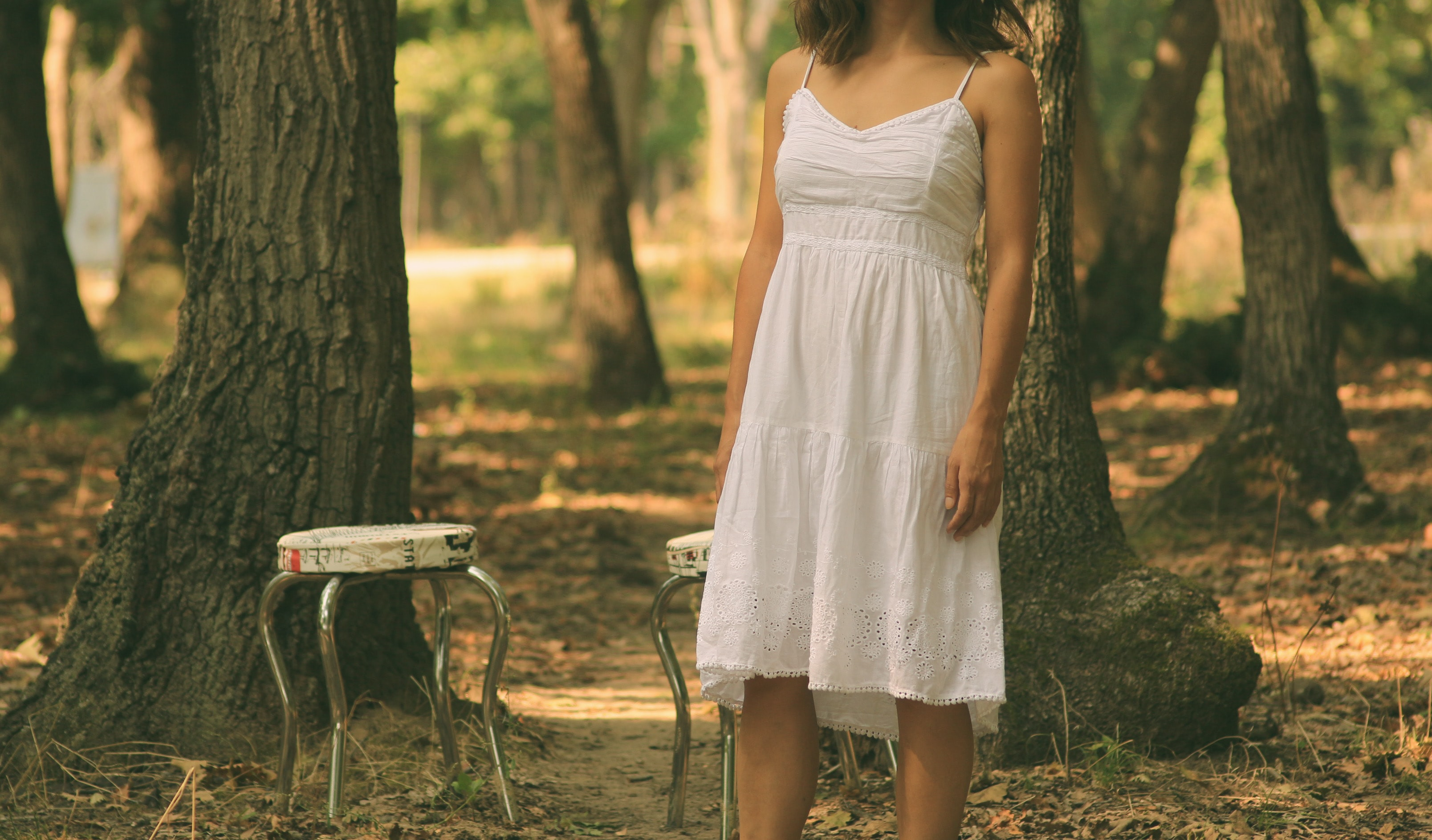woman in white spaghetti strap dress standing in front of white stool