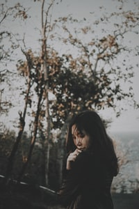 vignette photography of woman near tree