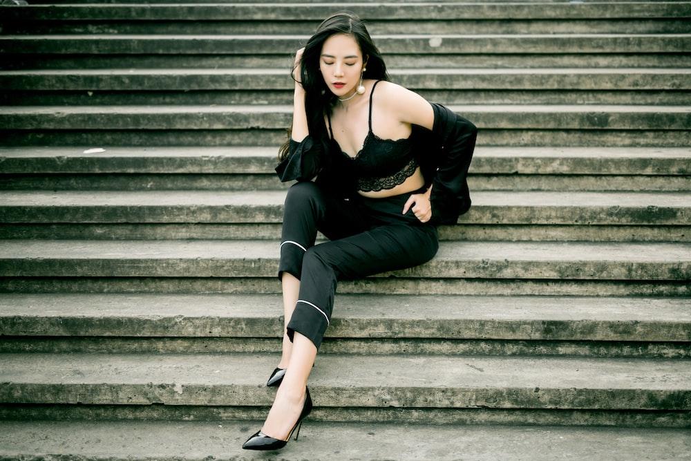 woman wearing black bralette, jacket, and capri pants posing on stairs