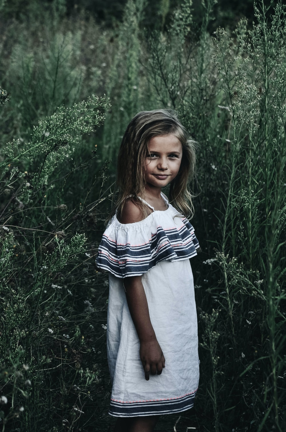 girl standing near tall grasses