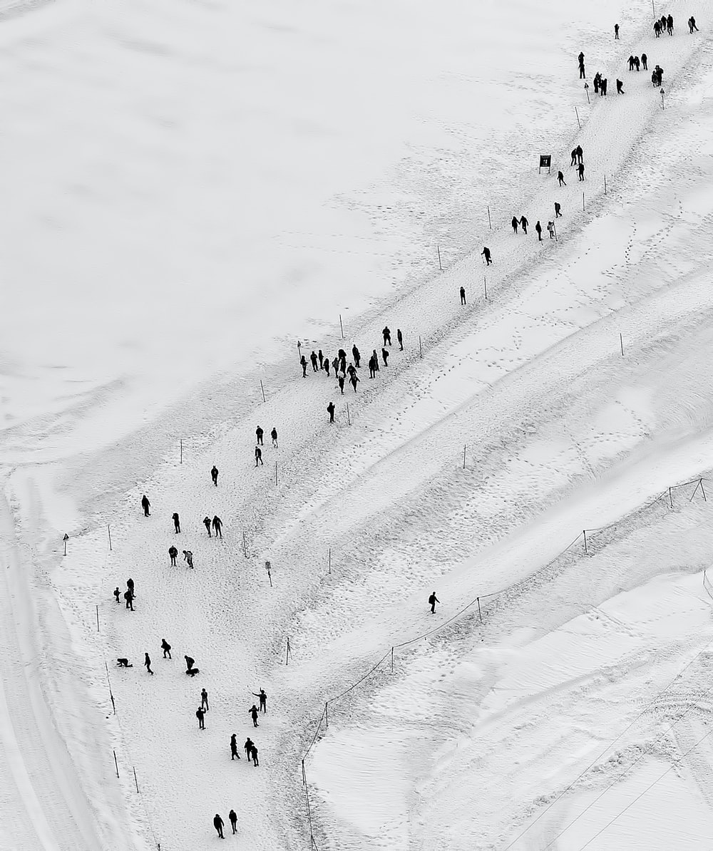 people walking on snow field at daytime