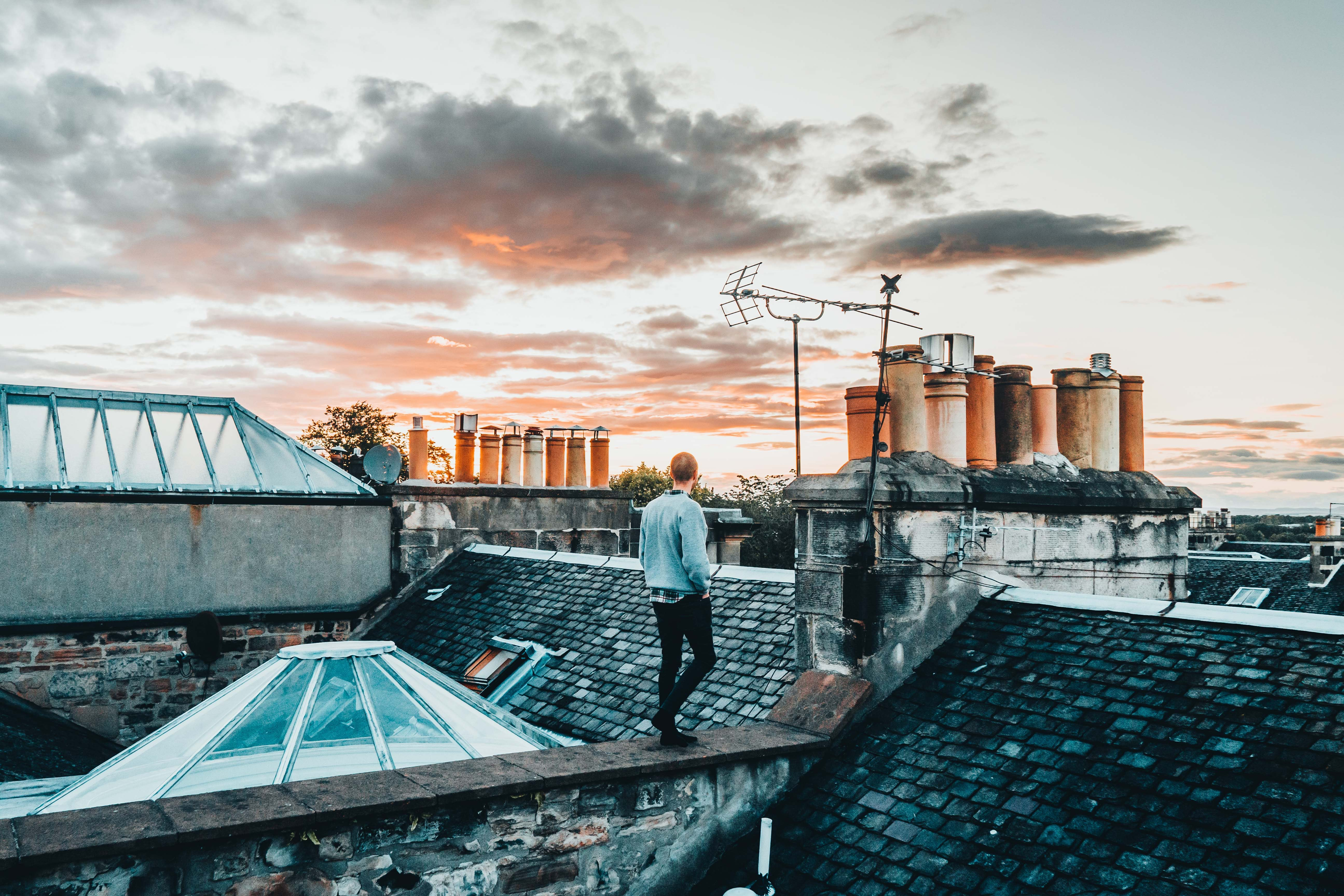 man in gray sweater standing on roof abn
