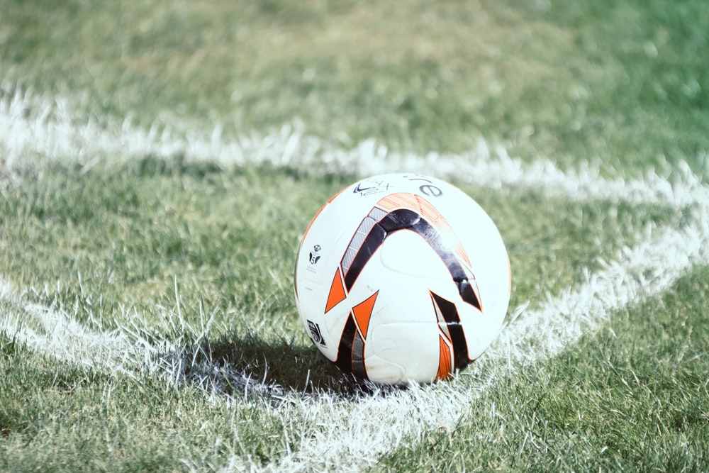 white, orange, and black soccer ball on field