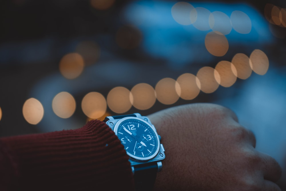 bokeh photography person wearing round silver-colored chronograph watch