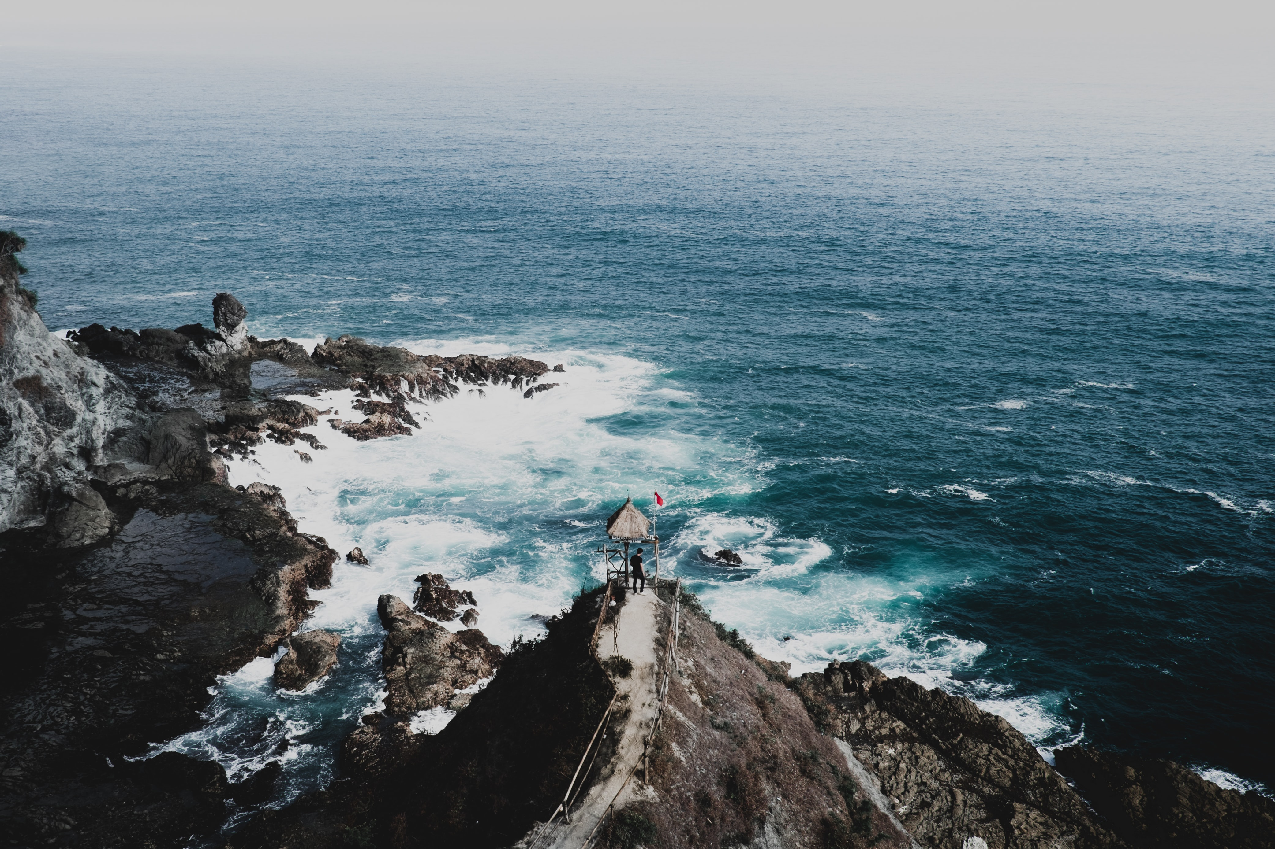 person standing on cliff facing green sea