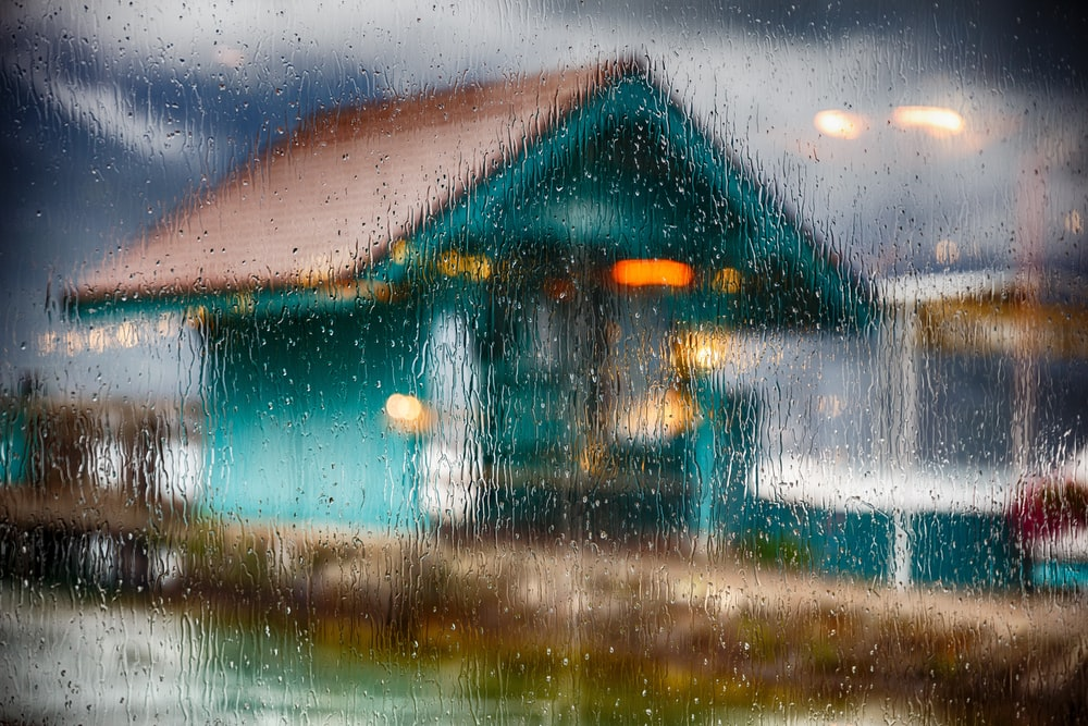 window glass filled with water drops and a view of teal wooden house