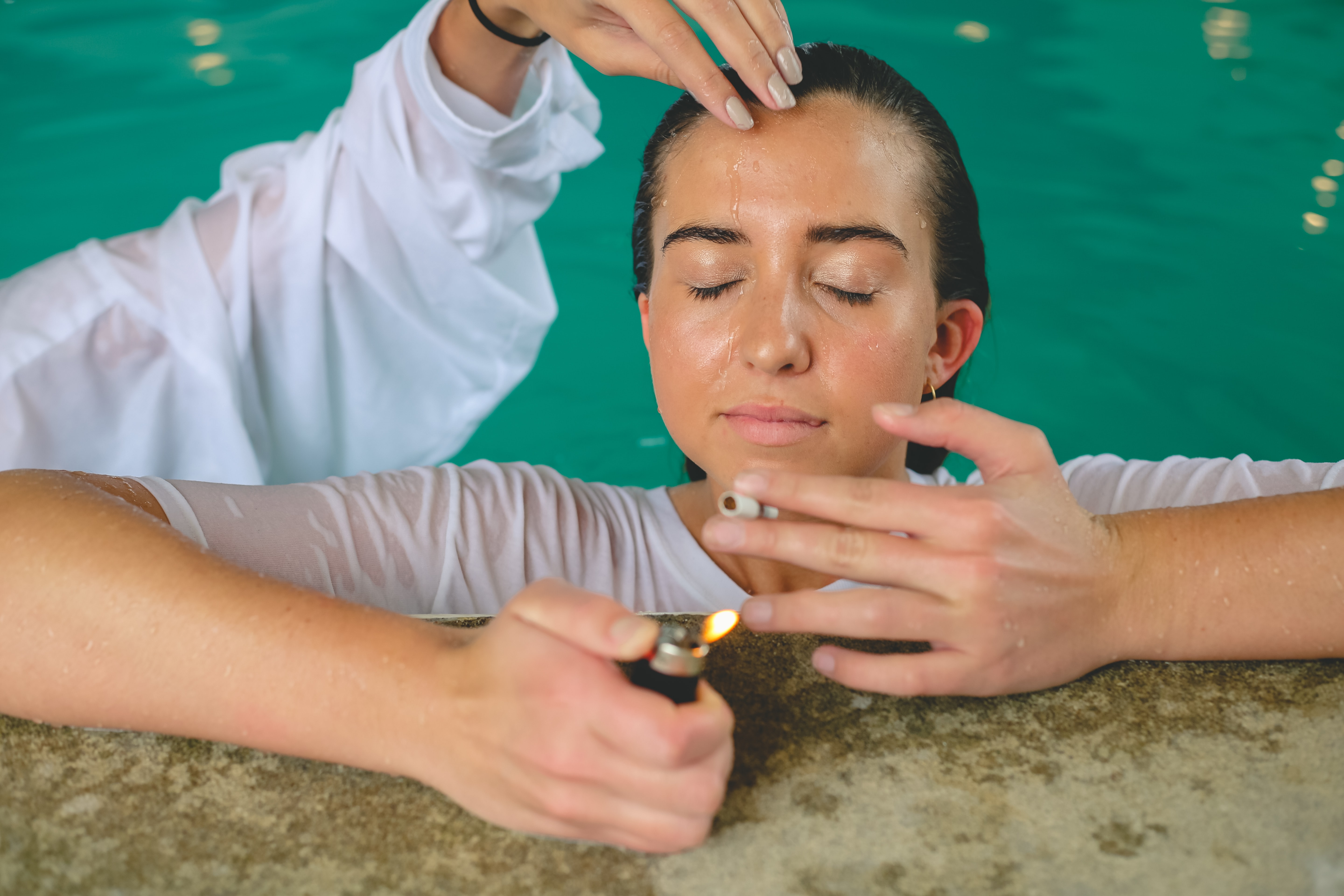 woman soak in water holding cigarette stick and lighter