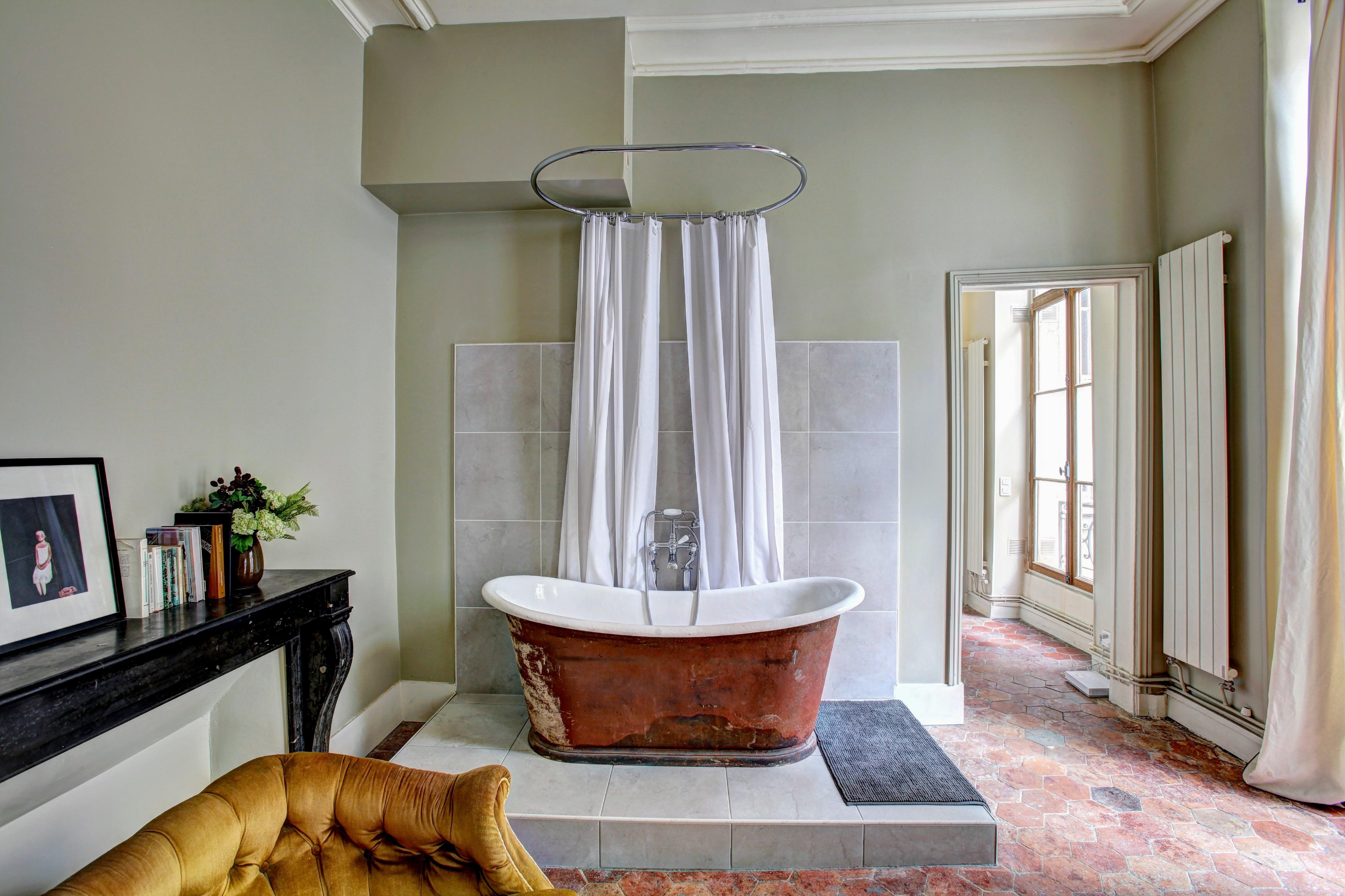 red and white bathtub near yellow fabric sofa