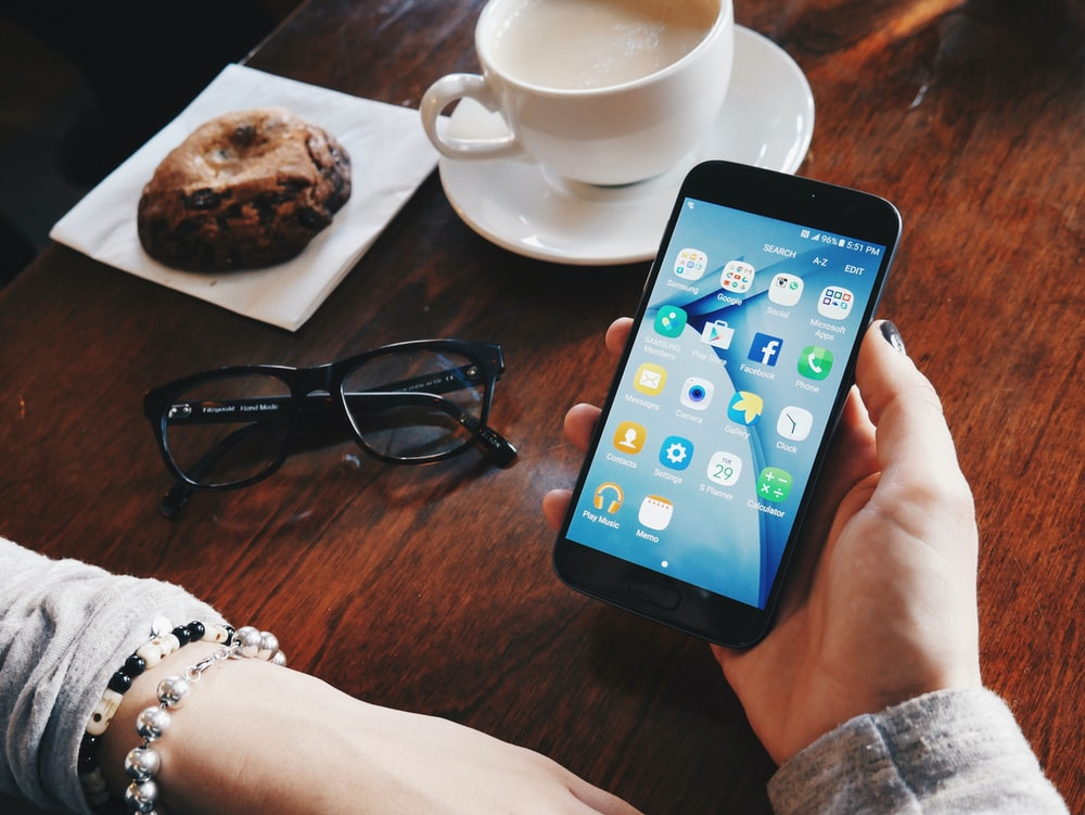person holding turned-on smartphone sitting at table with filled cup with saucer