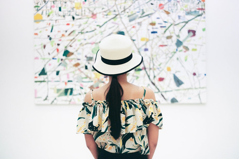 woman standing in front of abstract painting