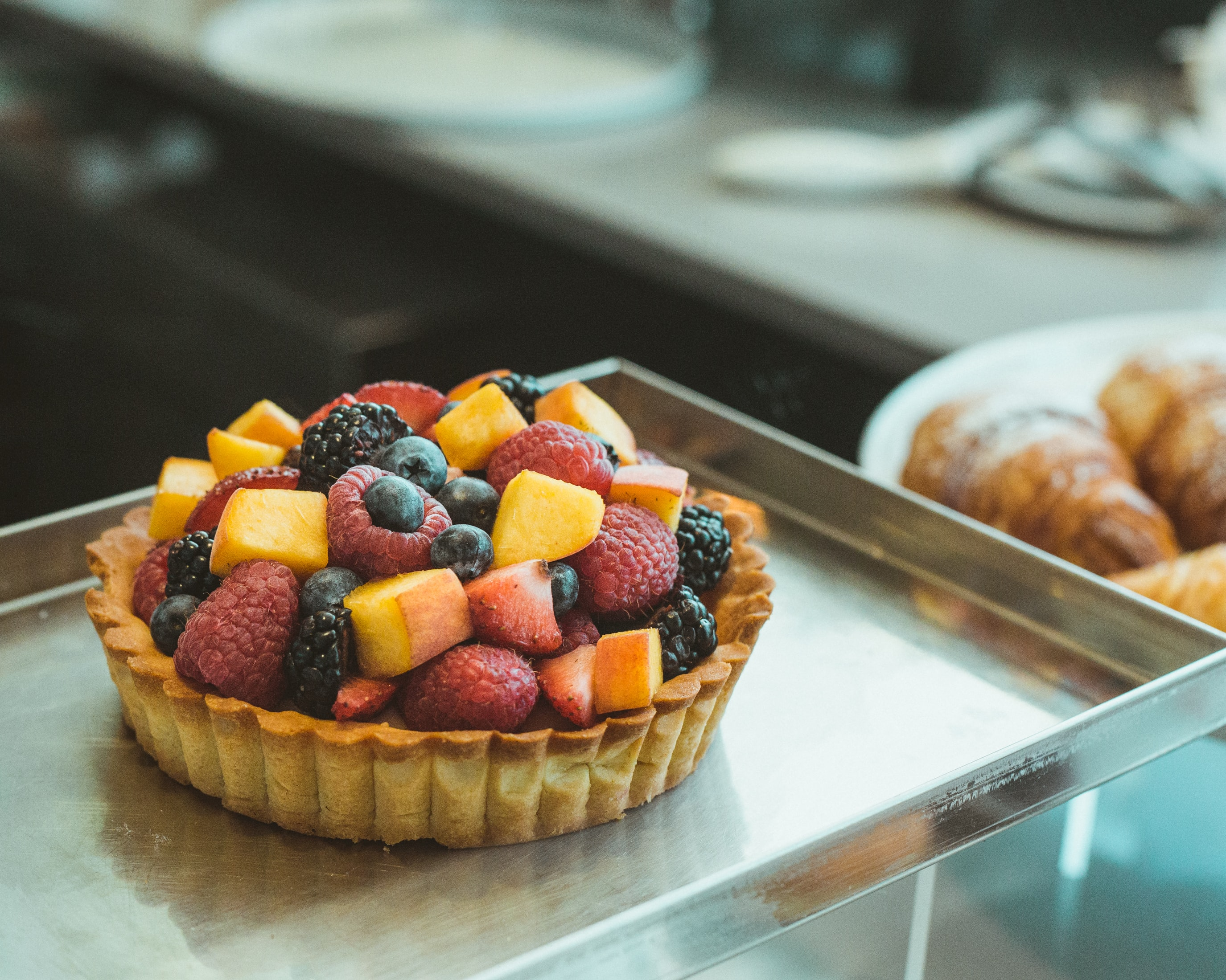 brown pastry with assorted fruits on top